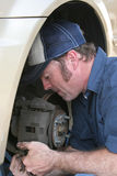 Skilled Auto Mechanic. A closeup of an auto mechanic concentrating as he fixes a car royalty free stock images