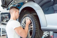 Skilled auto mechanic replacing the rims of a car in a trendy repair shop. Skilled auto mechanic replacing the rims of a lifted car during work in a trendy Stock Image