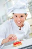 Skilled baker finishing tart Stock Photography