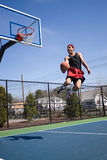 Skilled Basketball Player. A young athlete flying through the air towards the basketball hoop for a lay up or slam dunk Royalty Free Stock Photos