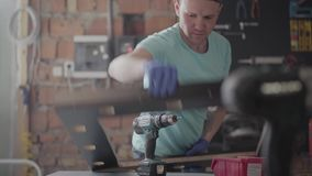 Portrait professional carpenter cutting a piece of wood in his woodwork workshop, using a circular saw with other. Skilled bearded carpenter cutting a piece of stock footage