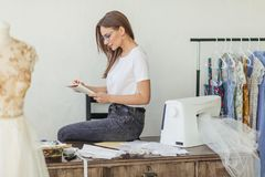 Fashion designer at work. Talanted dressmaker drawing sketch at her workspace. Skilled beautiful dressmaker in fashion atelier in stylish eyeglasses and white stock photography