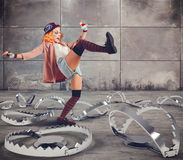 Skilled and brave clown. Clown walks with skills between big traps stock image