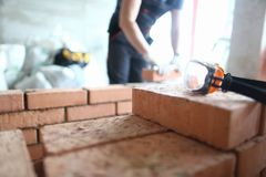 Skilled bricklayer working. Focus on construction site made of red bricks and concrete. Professional engineer stacking special equipment and tools to properly stock photo