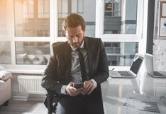 Skilled businessman is holding mobile phone in office. Important message. Serious bristled man in suit is sitting in chair and using modern smartphone. He is Royalty Free Stock Image