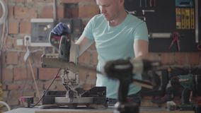 Skilled carpenter cutting a piece of wood in his woodwork workshop, using a circular saw with other machinery in the. Skilled bearded carpenter cutting a piece stock footage