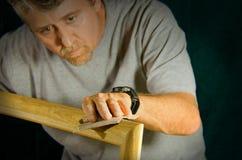 Skilled carpenter man sanding wood frame. Carpenter contractor man skillfully sanding and preparing wooden molding for door framing on home interior repair Stock Images
