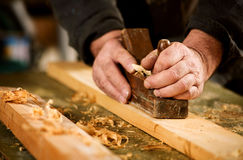 Skilled carpenter using a handheld plane. To smooth and level the surface of a plank of hardwood, close up view of his hands, the tool and wood shavings Stock Images