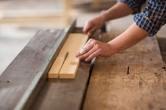 Skilled carpenter working in his woodwork workshop, using a circ Royalty Free Stock Images
