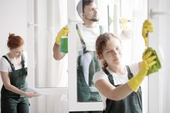 Skilled cleaning team washing windows. Skilled cleaning team washing the windows. Home cleaning service concept Royalty Free Stock Photo