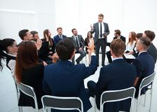 Skilled coach asks questions to the participants of the training. Photo with copy space Royalty Free Stock Photo