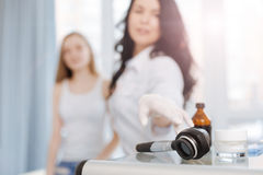 Skilled cosmetologist using dermatoscope for skin examination in the clinic Stock Images