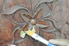Skilled craftsman adding gold leaf skin to the wood carving Stock Photo