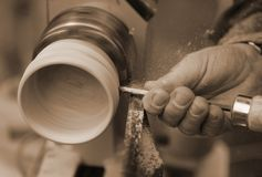Skilled craftsman with the chisel during the work of the wood pi. Hand of a Skilled craftsman with the chisel during the work of the WOOD piece with the lathe in royalty free stock photo