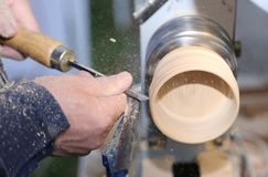 Skilled craftsman with the chisel during the work of the wood pi. Ece with the lathe in the carpentry Stock Images