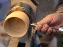 Skilled craftsman with the chisel during the work of the wood pi. Ece with the lathe in the carpentry Royalty Free Stock Image