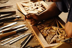 Skilled craftsman doing wood carving using traditional method Stock Photo