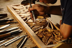 Skilled craftsman doing wood carving using traditional method Stock Image