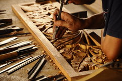 Skilled craftsman doing wood carving using traditional method Royalty Free Stock Photos