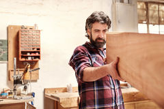 Skilled craftsman inspecting a wooden plank for quality of cut Royalty Free Stock Photography