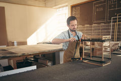 Skilled craftsman manufacturing a display case in wood worksho Royalty Free Stock Image