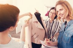 Skilled dressmakers spending working hours together. Accurate work. Close up of skilled dressmakers taking measurements and putting down necessary information Stock Image