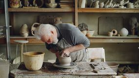 Skilled elderly potter is producing ceramic pot on turning wheel in workplace. Creation process, traditional pottery and. Skilled elderly male potter is stock video footage