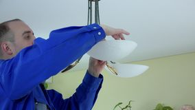 Skilled electrician install eco light bulbs in chandelier at client home. stock footage