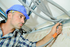 Skilled electrician wiring house. Skilled electrician wiring a house stock photography