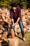 Skilled forester. Full length of confident young forester cutting log while standing outdoors Stock Image