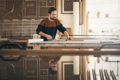 Skilled framer and craftsman at work in his studio. Young professional framer using specialised tools in his workshop studio while concentrating on craftsmanship Stock Photography