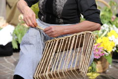 skilled hands of an elderly woman while twist the straw of a bag Stock Image