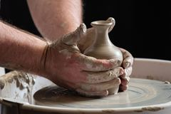 The skilled hands of a potter. A very close up photograph of the hands of a skilled potter throwing a pot on the wheel and finishing the final pot smoothing and Royalty Free Stock Photos