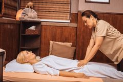Serious skilled Asian masseuse performing the massage. Skilled hands. Serious skilled masseuse performing the massage while working in the spa salon stock images