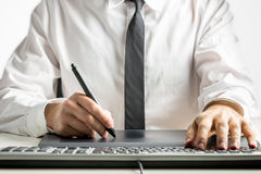 Skilled male designer drawing on a graphics tablet. Close-up of the hands of a skilled male designer wearing white shirt and black tie while drawing on a Stock Photos