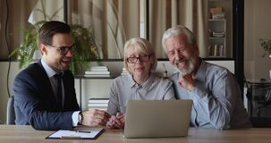 Skilled male financial advisor showing computer presentation to old clients.