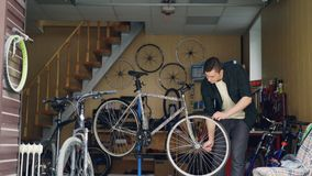 Skilled male mechanic is fixing bicycle wheel with wrench then turning it and checking. Many cycles, spare parts, tools. Skilled male mechanic is fixing broken stock footage
