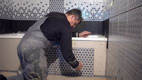 Skilled man lay tiles on bathtub side in bathroom