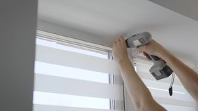 Skilled man is spinning screw for fixing fastener on window, using recharged screwdriver in a room of modern apartment. Close-up of his hands stock video footage