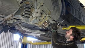 Skilled mechanic removing worn car parts in garage under automobile. Skilled mechanic removing worn broken car parts with huge screwdriver in garage under the stock video