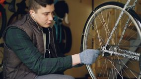 Skilled mechanic is rotating bicycle wheel checking mechanism and turning treadle while fixing bike. Professional cycle. Skilled male mechanic is rotating stock video