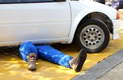 Skilled mechanic with the suit from work while repairing the eng. Ine failure of the car Stock Image
