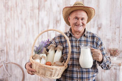 Skilled old farm worker is presenting healthy food Stock Image