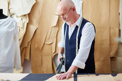 Skilled Senior  Tailor Working in Small Atelier Stock Photo