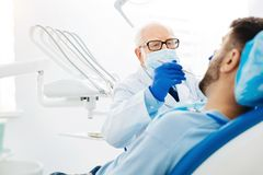 Skilled stomatologist using dental instruments Royalty Free Stock Images