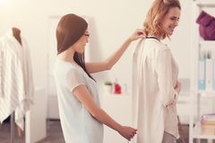 Skilled tailor taking measurements of pleasant woman. Attention to work. Waist up of skilled pretty tailor taking measurements of pleasant women while standing Royalty Free Stock Image