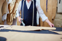 Skilled Tailor Working with Patterns in Atelier Royalty Free Stock Photography