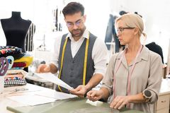 Skilled Tailors in Atelier. Waist up portrait of two tailors making patterns while working in atelier workshop royalty free stock image