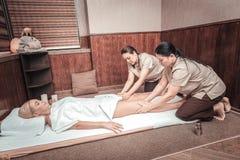 Skilled Thai massage therapists massaging female legs. Body procedure. Skilled Thai massage therapists massaging female legs while doing their job stock photo