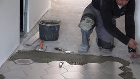 Skilled tiler lay hexagon floor tiles in corridor